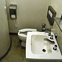 Figuur - bijzondere wc waar je met je knieën tegen de muur mag zitten.