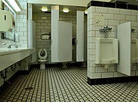 Figuur - Bij het linker urinoir kunnen voorbijgangers en mensen die hun handen staan te wassen (via de spiegel) vrolijk met je mee kijken.