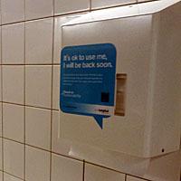 """Figuur X - """"It's ok to use me, I will be back soon."""" valt er te lezen op de papieren handdoekjes dispenser op Schiphol."""