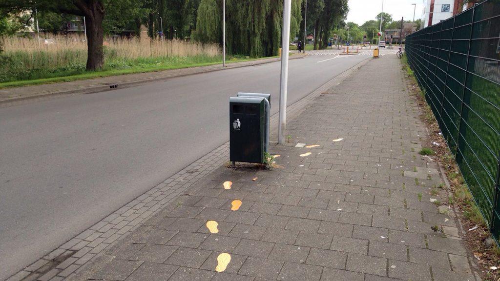 Voetstappen op de stoep lopen naar een afvalbak. We hebben onderzocht of dit er toe leidde dat mensen meer afval in de afbak gooiden.